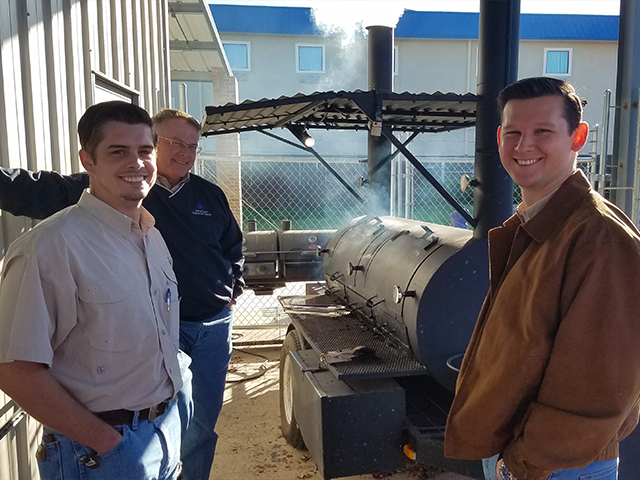 three men smiling with a cooker