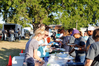 Employees serving people at a cookout