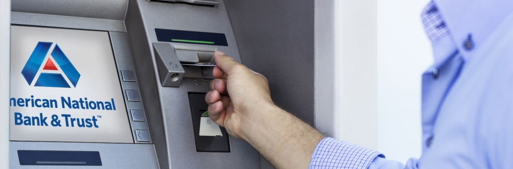 man putting card into atm