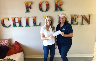 Meagan Swenson presenting a check to a charity