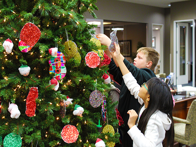 A pair of students from Fowler Elementary decorating Christmas tree.