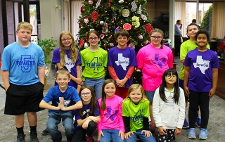 Group of students smiling in front of Christmas Tree from Fowler Elementary.