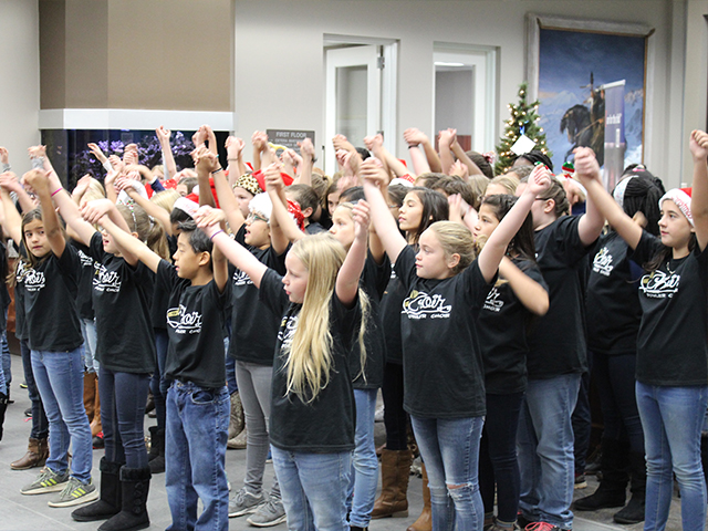 Group of children sining with arms raised for Fowler Elementary.