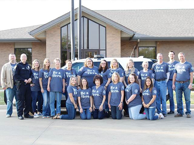 Our mortgage division employees smiling while wearing Be a Hero shirts in the parking lot and posing with a WFPD officer.
