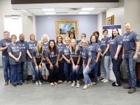 A group of employees at the main bank smiling while wearing Be a Hero shirts.