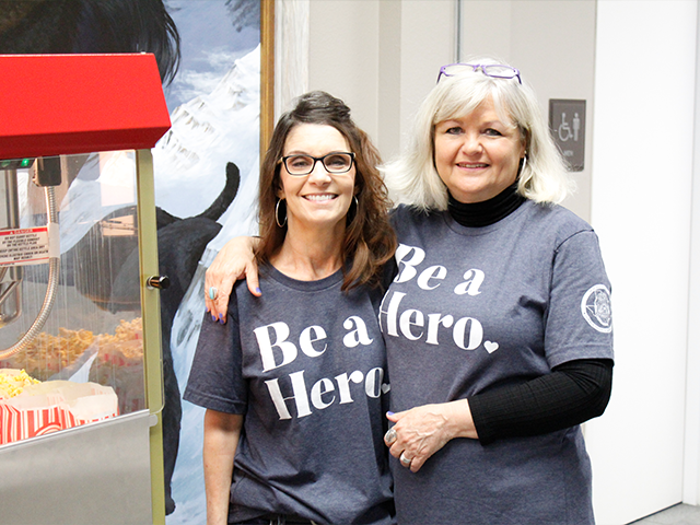 Two employees smiling while wearing Be a Hero shirts.