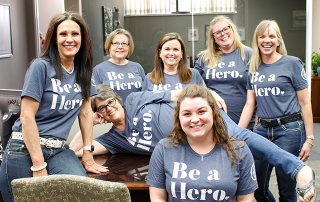 Trust department employees wearing Be a Hero shirts while smiling.