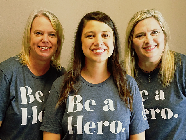 Archer City Branch employees smiling while wearing Be a Hero shirts.